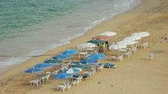 People enjoy the beach sitting under beach umbrellas Stock Footage