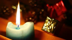 Blue candle with small golden and red gift boxes for Holidays Stock Footage