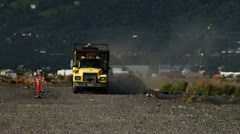 Dump Truck with Scrap Metal on Dusty Road - long shot Stock Footage