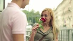 Young man giving rose to his girlfriend in the city, steadicam shot HD Stock Footage