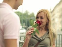 Young man giving rose to his girlfriend in the city, steadicam shot NTSC - stock footage