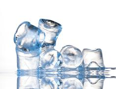 several ice cubes on glass table - stock photo