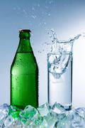 Bottle of mineral water with ice and a glass with water splash Stock Photos
