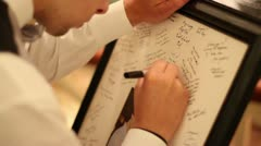 Man Writing Note on Picture at Wedding Stock Footage