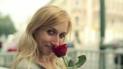 Woman with red rose flirting with camera, steadicam shot HD Stock Footage