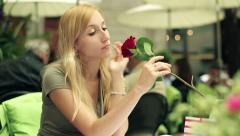 Young beautiful sad woman with rose in cafe, steadicam shot HD Stock Footage