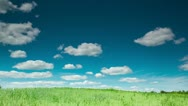 Blue sky and green meadow, time lapse with running clouds and shadows Stock Footage