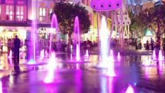 HD night time lapse of people at colourful fountain area Stock Footage