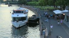 Double deck boat docked along busy walkway (HD) c Stock Footage