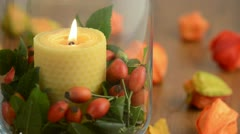 Extinguish a candle in glass with rose hips. Stock Footage