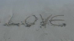 Writing on wet sand Stock Footage