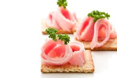 crackers canapes with ham and parsley - stock photo