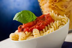 Pasta with tomato sauce and basil on blue background Stock Photos