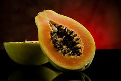 papaya on shiny glass table - stock photo