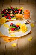 pie with fruits and petals illuminated by candle light - stock photo
