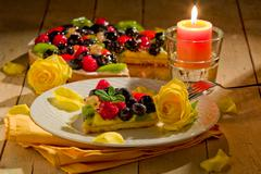 Pie with fruits and petals illuminated by candle light Stock Photos