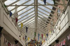 colourful bunting flags in a glass rooved walkway in an english town. - stock photo