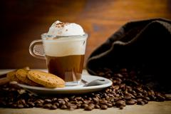 Cappuccino on coffee beans Stock Photos
