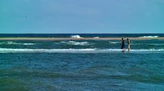 Women walk on sandbar at ocean Stock Footage