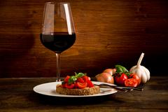 bruschetta appetizer with red wine on wooden table - stock photo