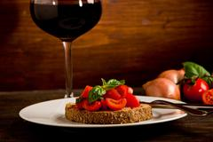 Stock Photo of bruschetta appetizer with red wine on wooden table