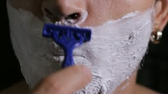 Man shaves disposable razor close up Stock Footage