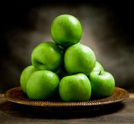 Green apples inside a basket Stock Photos