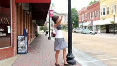 Cute short haired teenaged girl swinging around lamp post while downtown Stock Footage