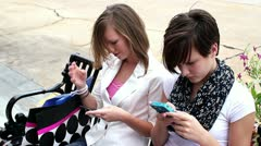 Close up of 2 teen aged girls texting on their smart phones - stock footage