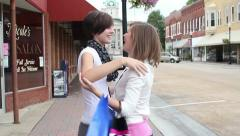 Two friends run into each other while shopping and hug and greet - stock footage