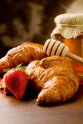 croissants with honey and strawberries - stock photo