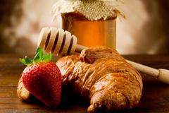 Stock Photo of croissants with honey and strawberries
