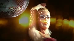 Gogo dancing next to a large spinning discoball Stock Footage