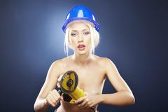 Blonde model holds an angle grinder. - stock photo