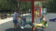 Little girl with mother in park, playground, carousel. Stock Footage