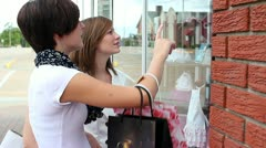 Two attractive teen aged girls shopping with bags of purchased items - stock footage