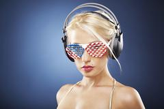 Portrait of blond girl in gold swimwear and american inspired accessories. - stock photo