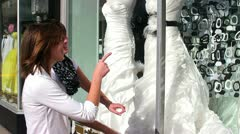 Two teenaged girls window shopping for a wedding dress Stock Footage