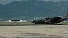 C130 moving against mountainous background (HD) c Stock Footage