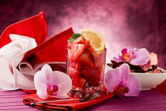 strawberries with orchid on red table - stock photo