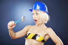 Shocked blonde model with a construction helmet and an adjustable wrench - stock photo