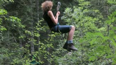 Woman on a Tyrolean Traverse along a cable through the forest Stock Footage