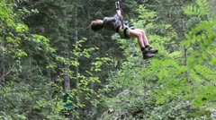 Young boy on a Tyrolean Traverse in a forest Stock Footage