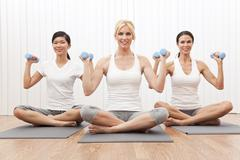 interracial yoga group of three women weight training - stock photo