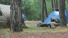 On a rainy day on a camp site a man repairs his tent Stock Footage