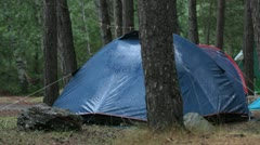 On a rainy day on a camp site a blue tent is getting wet Stock Footage