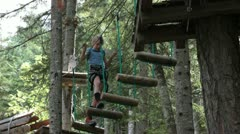 Girl climbing on a horizontal ladder in an adventure park on great height Stock Footage