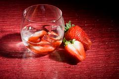 strawberries on ice on red background - cocktail dessert - stock photo