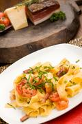 Pasta with bacon and tomatoes Stock Photos