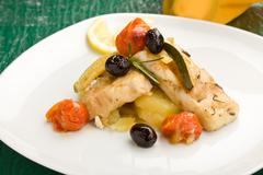 baked cod with olives and tomatoes - stock photo